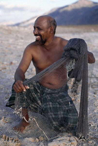 A fisherman near Di Hamri with his weighted throwing net, which he will use in shallow water to catch bait for line-fishing. The island's coastal population depends almost entirely on fishing as its principal source of livelihood with shark