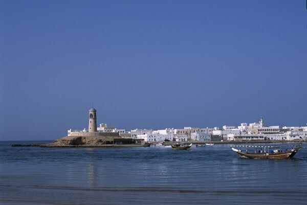 A fishing dhow motors across the lagoon towards the sea in front of the lighthouse and whitewashed houses of the village of Al Ayja behind