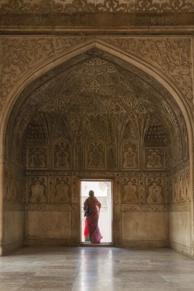 India, Uttar Pradesh, Agra, Agra Fort, a woman in a red saree walks through the interior of the Diwan-e-Khas (hall of private audiences), a building constructed by Shah Jahan in 1636