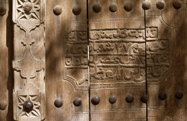 An inscription on the wooden door of the souq at Nizwa