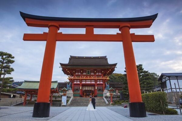 Japan, Kyoto, A wedding bride and groom pose at Fushimi Inari Shrine
