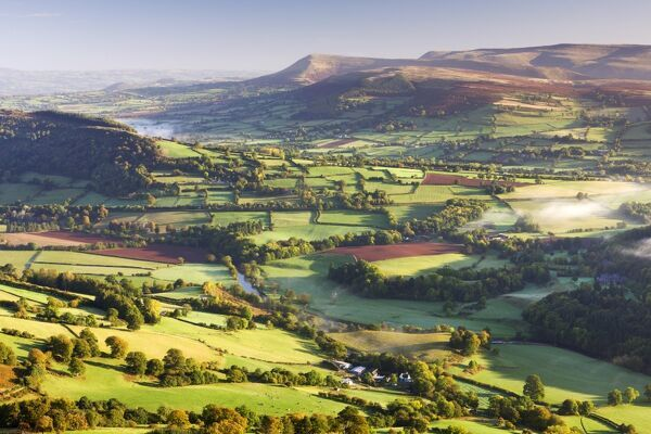 Morning sunshines illuminates the patchwork fields in the Usk Valley, looking towards the Black Mountains, Brecon Beacons National Park, Powys, Wales, UK. Autumn (October) 2009