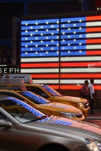 People walking past Neon sign of American Flag on Times Square, New York, Manhattan, USA