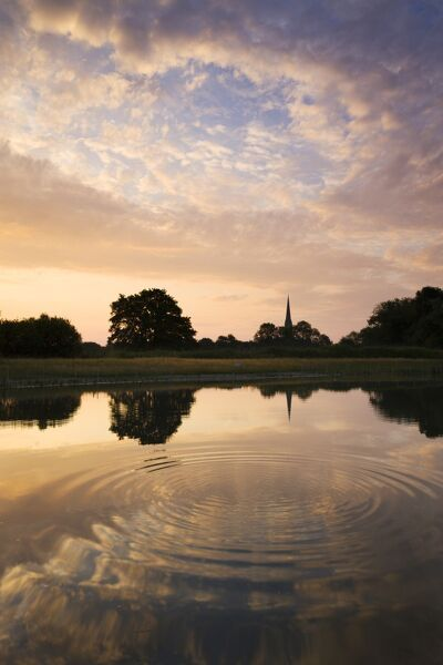 Salisbury Cathedral Spire and a beautiful dawn sky reflected in a rippled pond, Salisbury, Wiltshire, England. Summer (June) 2010