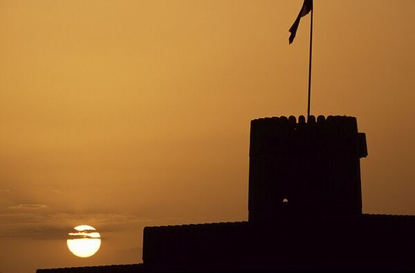 Silhouette of one of the towers of Ras al Hadd Castle at sunset. The 450 year old castle stands looking out to sea. It has 3 towers and a courtyard large enough to take all of the villagers when they were threatened with invasion. An escape tunnel
