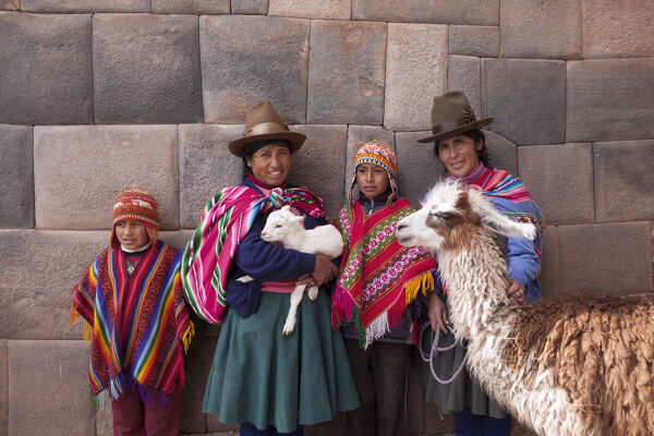 South America, Peru, Cusco. Quechua people standing in front of an Inca wall, holding a lamb and a llama and wearing traditional clothing including a bowler hat, liclla, chullo and poncho - while talking on a cell phone in the