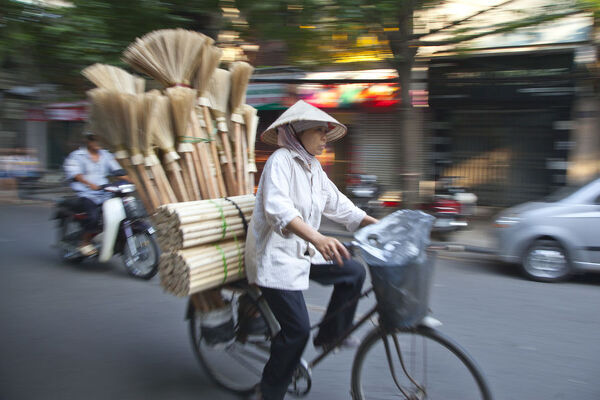 Woman carrying brooms on her bike, Old Quarter, Hanoi, Vietnam