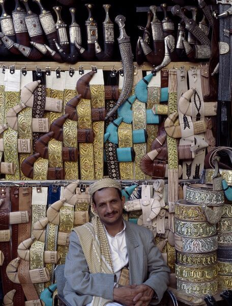 Yemeni trader sells traditional daggers at his stall in old Sana'a. Every male Yemeni wears a jambiya (a curved dagger) on a finely decorated belt. It is always worn in front of the body with the tip of the sheath pointing to the right. In this
