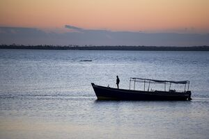 A boat arrives at the Ilha do Mozambique at sunset