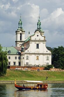 Church overlooking Boat on Vistula River, Krakow, Poland