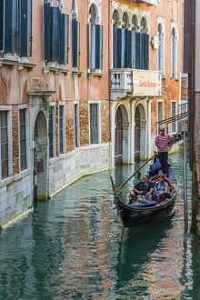 Gondola boat passing through a narrow canal, Venice, Veneto, Italy