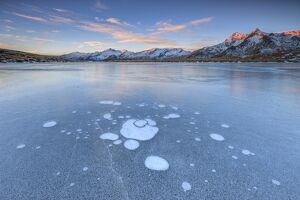 Ice bubbles on the frozen surface of Andossi Lake at sunrise Spluga Valley Valtellina