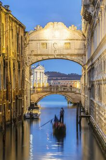 Italy, Veneto, Venice. Bridge of sighs illuminated at dusk with gondolas