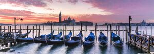 Italy, Veneto, Venice. Row of gondolas moored at sunrise on Riva degli Schiavoni