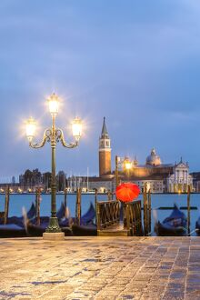 Italy, Veneto, Venice. Woman with red umbrella on Riva degli Schiavoni at dawn (MR)