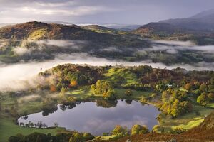 Loughrigg Tarn surrounded by misty autumnal countryside, Lake District, Cumbria, England