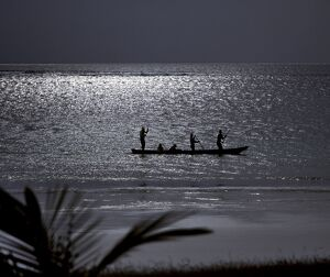 Three men pole a dugout canoe by moonlight in shallow water along Diani Beach.