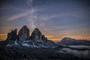 The Milky Way with its stars appear in a summer night on the Three Peaks of Lavaredo