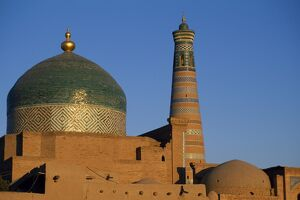 The minaret and tiled dome of a mosque rise above the