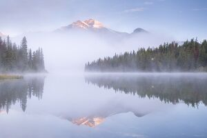 A mist shrouded Pyramid Mountain reflected in Pyramid Lake at dawn, Jasper National Park