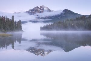 A misty Pyramid Mountain reflected in Pyramid Lake at dawn, Jasper National Park