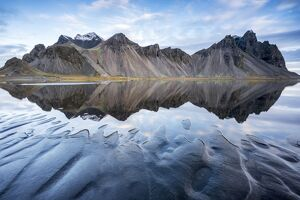 The mountains reflect on the surface of the ocean. Stokksnes, Eastern Iceland, Europe