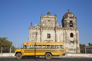 Nicaragua, Leon, American yellow bluebird bus driving past San Juan Church