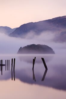 Old wooden jetty and St Herbert's Island on Derwent Water at dawn on a misty morning