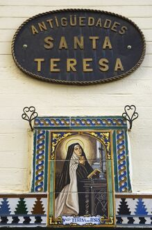 A painted ceramic mural depicting Santa Teresa praying before a cross