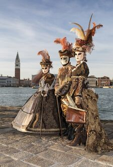 Three people in costume at Carnival time, San Giorgio Maggiore, Venice, Veneto, Italy