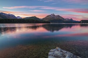 Pink sky at dawn illuminates the peaks reflected in Lake Sils Engadine Canton of