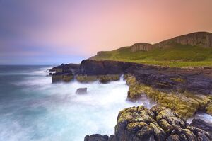 Rocky cliffs and sea, with wooden hills, Staffin bay, Isle of Skye, Scotland, UK