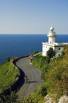 San Sebastian Bay Clifftop Lighthouse with Cyclist Riding uphill
