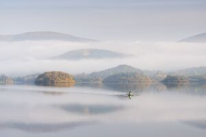 Single sculler rowing across a misty Derwent Water at dawn, Lake District, Cumbria