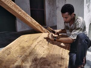 A skilled craftsman with traditional tools carves a