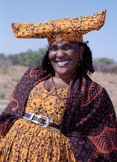 A smartly dressed Herero woman has a beaded AIDS badge
