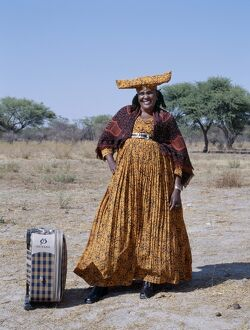 A smartly dressed Herero woman waits for a bus