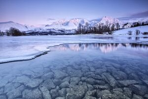 Snowy peaks are reflected in the frozen Lake Jaegervatnet at sunset Stortind Lyngen