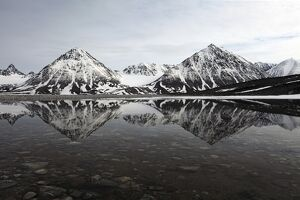 Spitsbergen, Svalbard, Norway. Mountains reflecting on a lagoon in northern spitsbergen