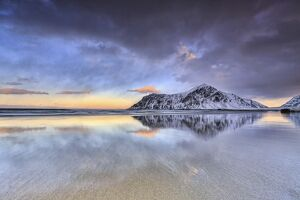 Sunset on Skagsanden beach surrounded by snow covered mountains reflected in the cold sea