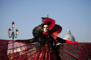 Venice, Veneto, Italy; A mask in costume on the Bacino di San Marco with the cupola