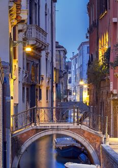 Venice, Veneto, Italy. View over a bridge and a canal at dusk