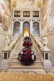 Woman in costume standing on staircase in Ca Segredo palace during Carnival, Venice