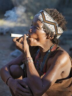 A woman from the N!!S hunter-gatherer band enjoys a smoke