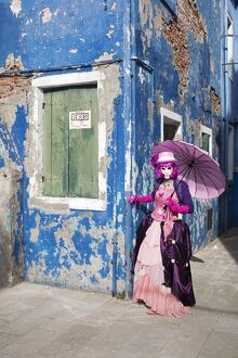 Woman in pink costume holding umbrella during Carnival, Island of Burano, Venice