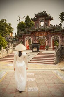 Woman wearing Ao Dai dress at Phouc Kien Assembly Hall, Hoi An (UNESCO World Heritage