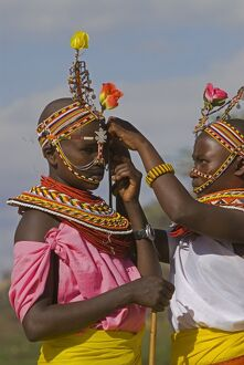 Two young Samburu girls help each other preparing for a celebration