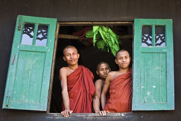 Myanmar, Burma, Rakhine State, Sittwe. Three novice monks look out of their dormitory window at the Pathain Monastery. Most early learning takes place in monastery schools