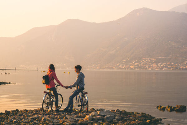 Pair of cyclists at sunset, iseo lake, Brescia province, Lombardy district, Italy