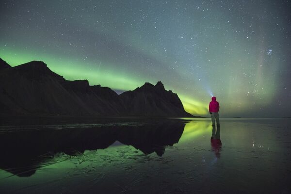 Stokksnes, Hofn, Eastern Iceland, Northern Europe. One man standing on the beach at night gazing at the northern lights and Vestrahorn mountain reflecting in the waters